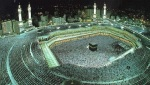 Thousands encircle the black stone, while an Imam speaks as the oracle of Allah.